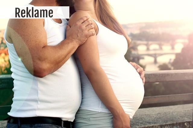 Gravid kvinde holdes om skulderen af mand.